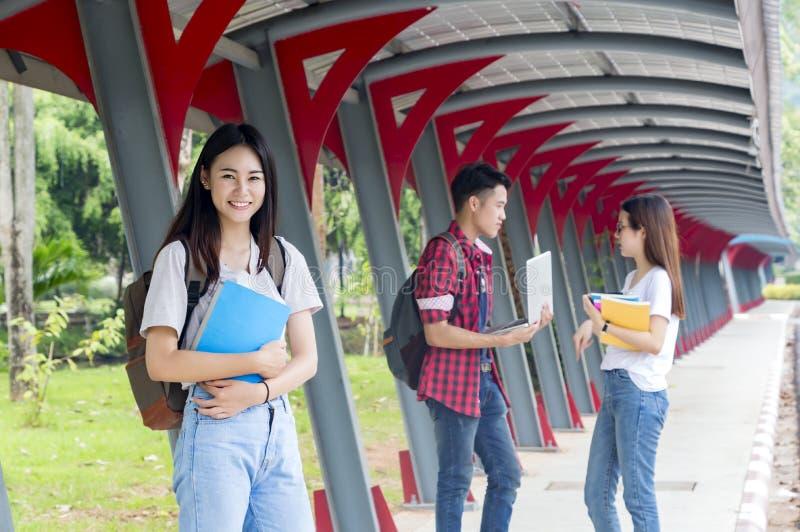 Groupe d'étudiants asiatiques d'université ayant l'amusement dehors, HOL de femme photo stock