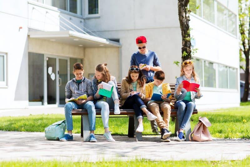 Groupe d'étudiants avec des carnets à la cour d'école photos stock