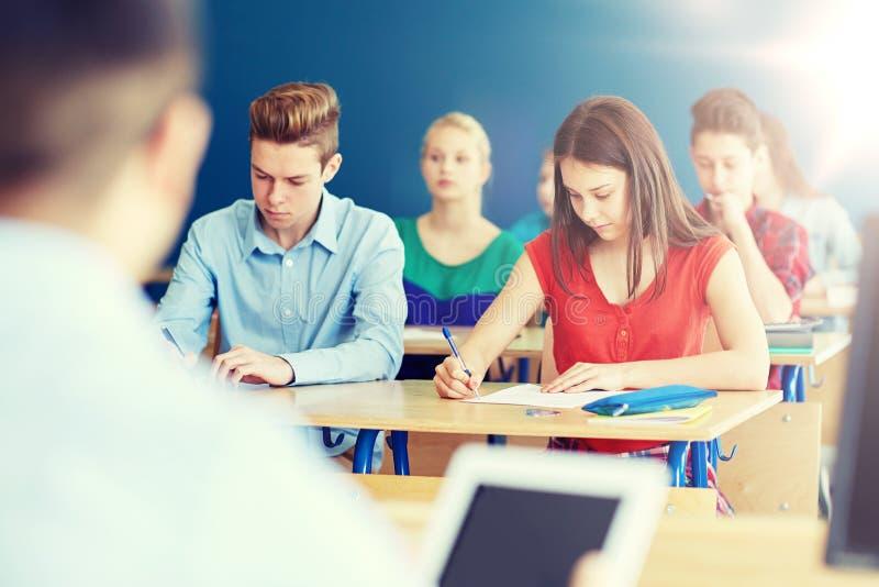 Groupe d'étudiants avec des livres écrivant l'essai d'école image libre de droits