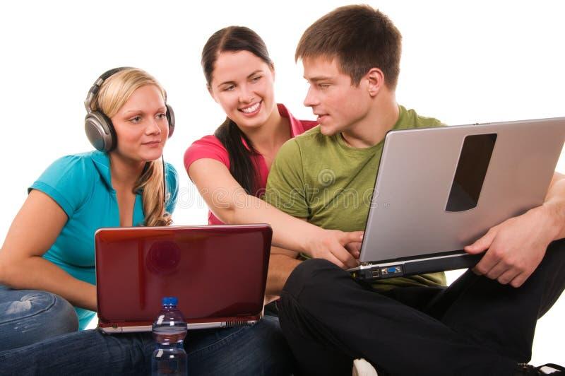 Groupe d'étudiants ayant l'amusement, effectuant à la maison le travail photo stock