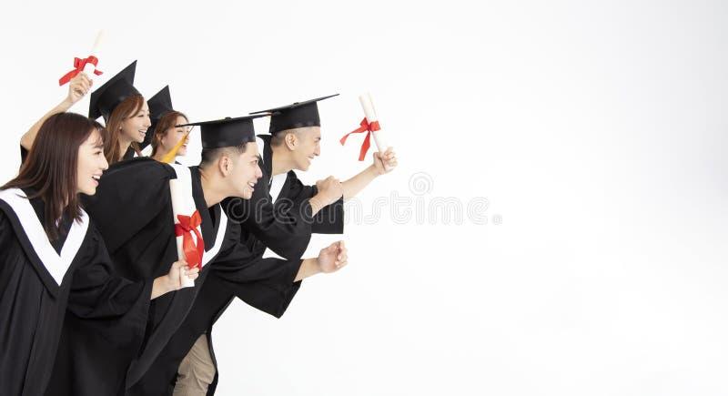 Groupe d'étudiants courant et célébrant l'obtention du diplôme photographie stock