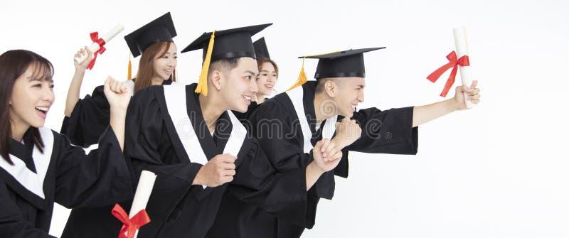 Groupe d'étudiants courant et célébrant l'obtention du diplôme photographie stock libre de droits
