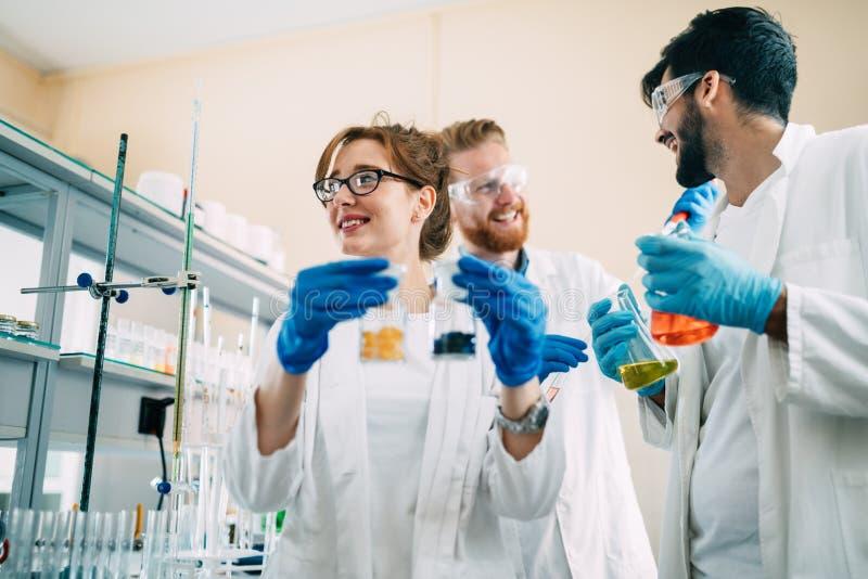 Groupe d'étudiants de chimie travaillant dans le laboratoire images stock