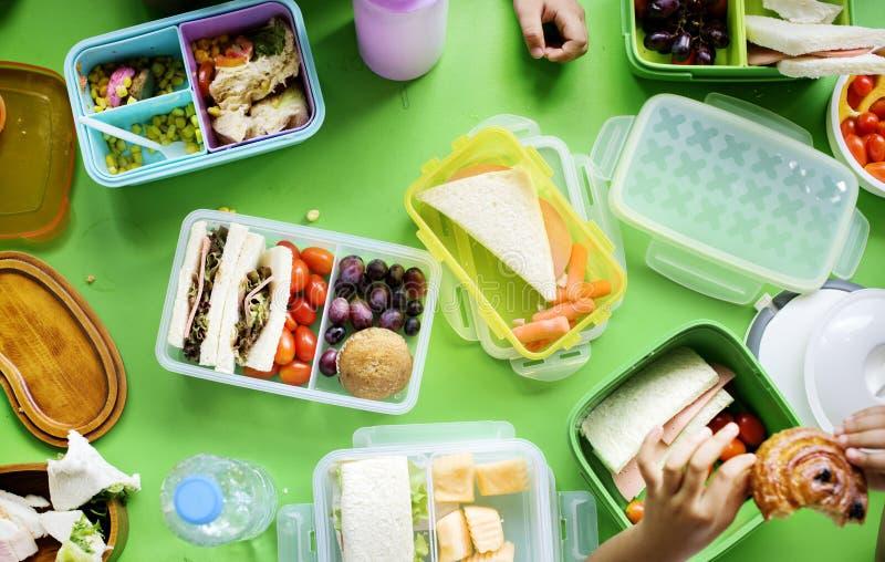 Groupe d'étudiants de jardin d'enfants mangeant la pause de midi de nourriture ensemble image stock