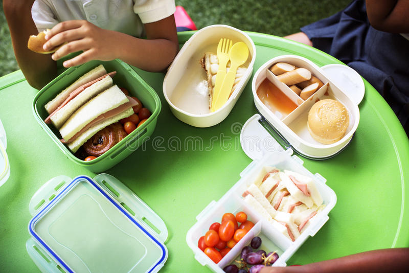 Groupe d'étudiants de jardin d'enfants mangeant la pause de midi de nourriture ensemble images stock