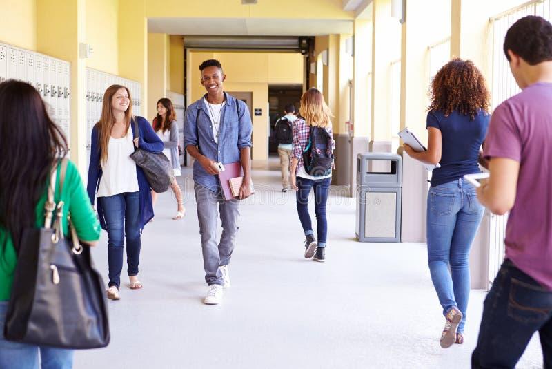 Groupe d'étudiants de lycée marchant le long du couloir images stock