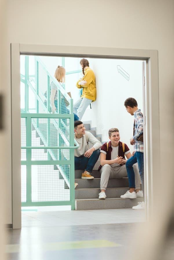 groupe d'étudiants de lycée passant le temps sur des escaliers à l'école photos libres de droits