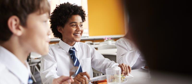 Groupe d'étudiants de lycée portant la séance uniforme autour du Tableau et mangeant le déjeuner dans le cafétéria photos stock