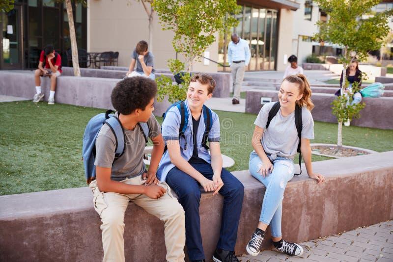Groupe d'étudiants de lycée traînant pendant le renfoncement images libres de droits