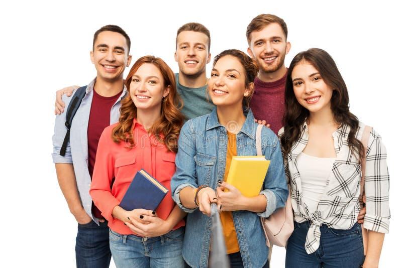 Groupe d'étudiants de sourire avec des livres prenant le selfie photo stock