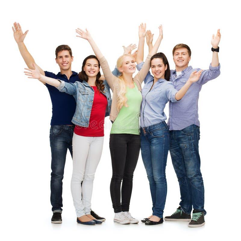 Groupe d'étudiants de sourire ondulant des mains photo stock