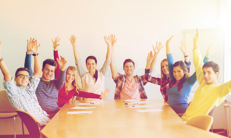 Groupe d'étudiants de sourire soulevant des mains dans le bureau photo stock