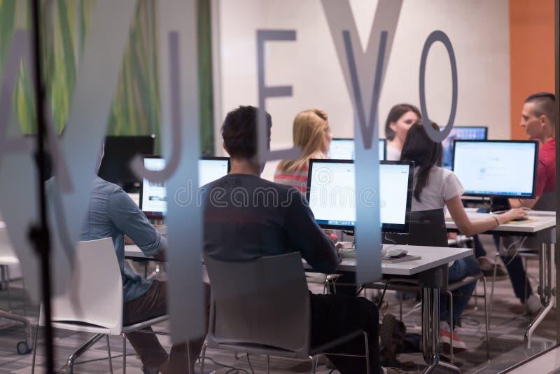 Groupe d'étudiants de technologie travaillant dans la classe d'école de laboratoire d'ordinateur photos stock