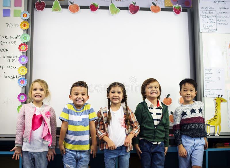 Groupe d'étudiants divers de jardin d'enfants se tenant ensemble dans les clas photographie stock