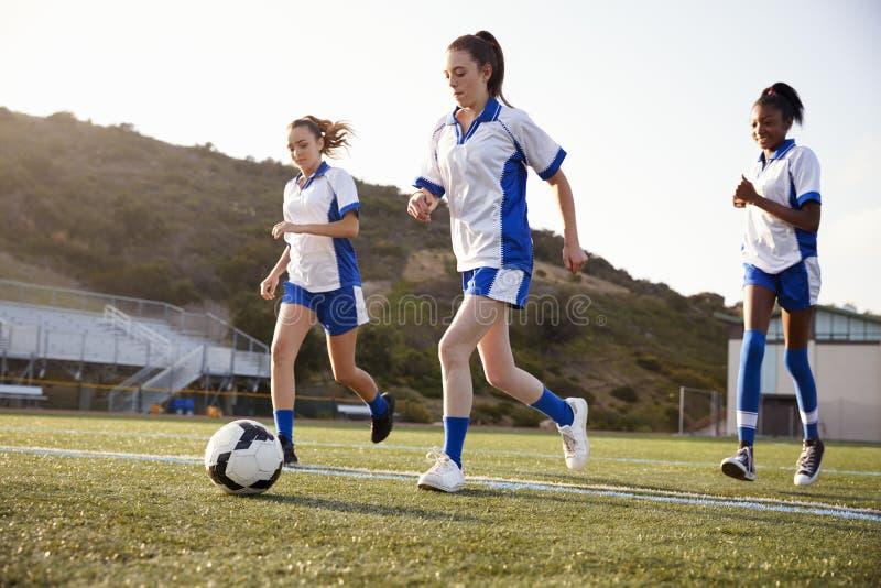 Groupe d'étudiants féminins de lycée jouant dans l'équipe de football photographie stock
