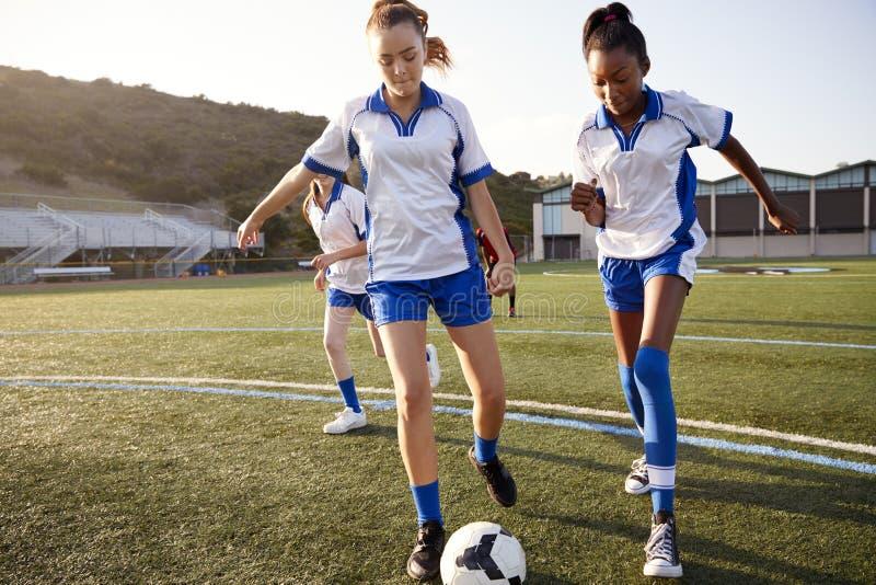 Groupe d'étudiants féminins de lycée jouant dans l'équipe de football photo stock