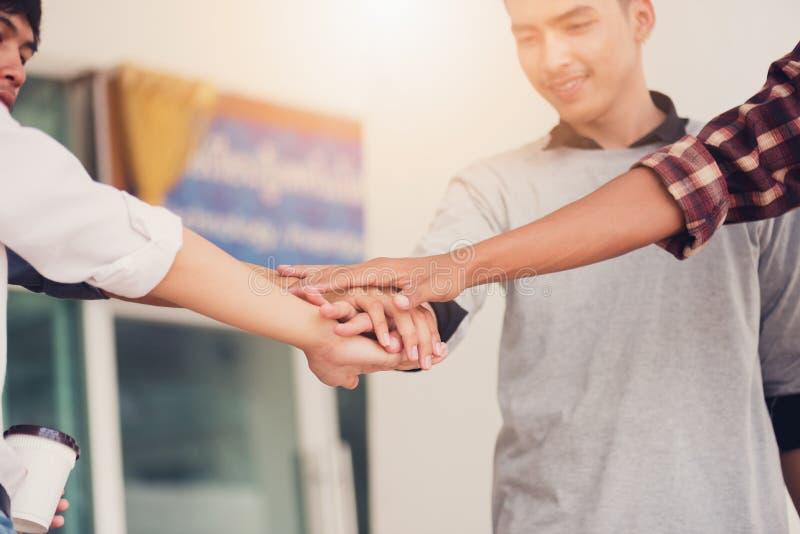 Groupe d'étudiants gais avec tenir les mains dans le campus, St photographie stock