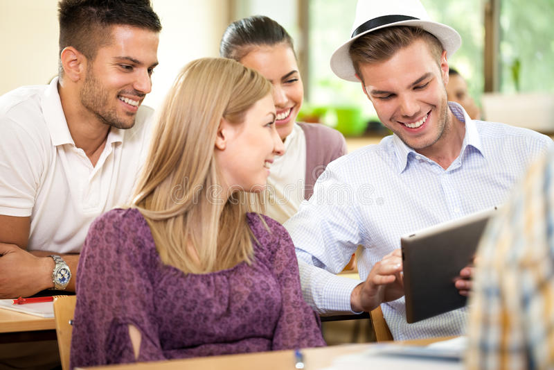 Groupe d'étudiants heureux avec le PC de comprimé image stock