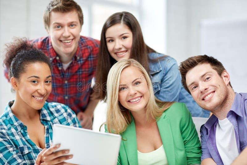 Groupe d'étudiants heureux de lycée avec le PC de comprimé images libres de droits