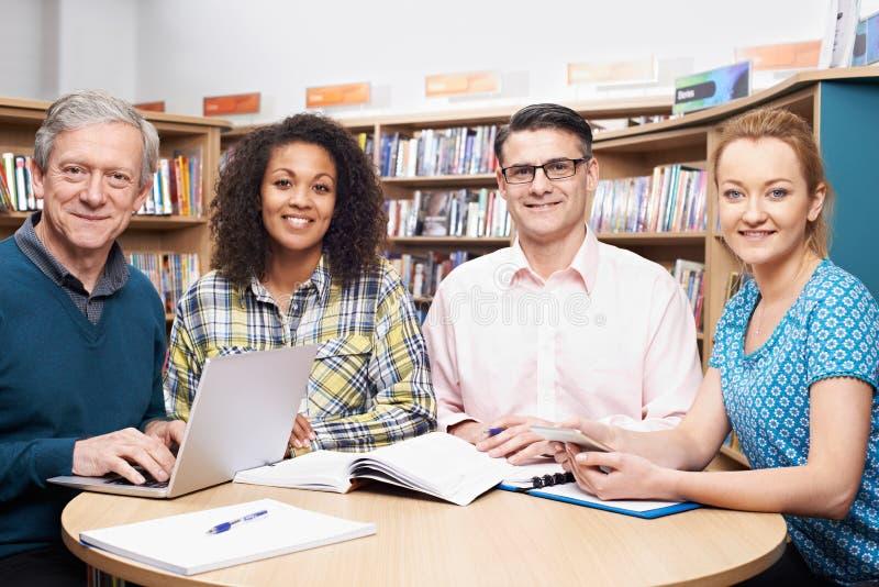 Groupe d'étudiants mûrs étudiant dans la bibliothèque images libres de droits