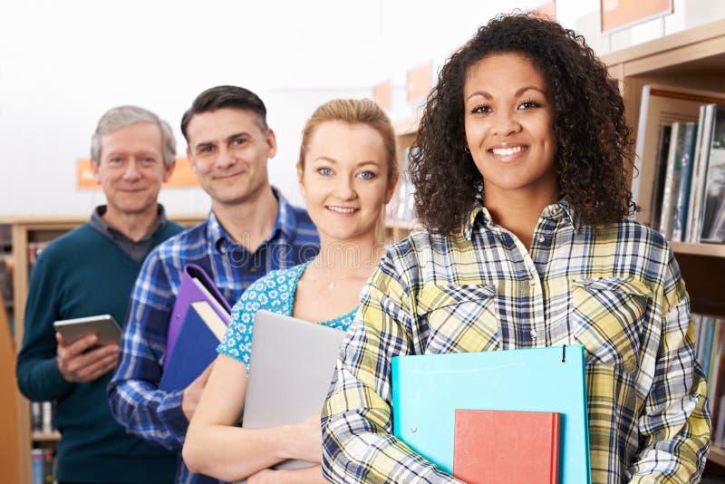 Groupe d'étudiants mûrs étudiant dans la bibliothèque image libre de droits