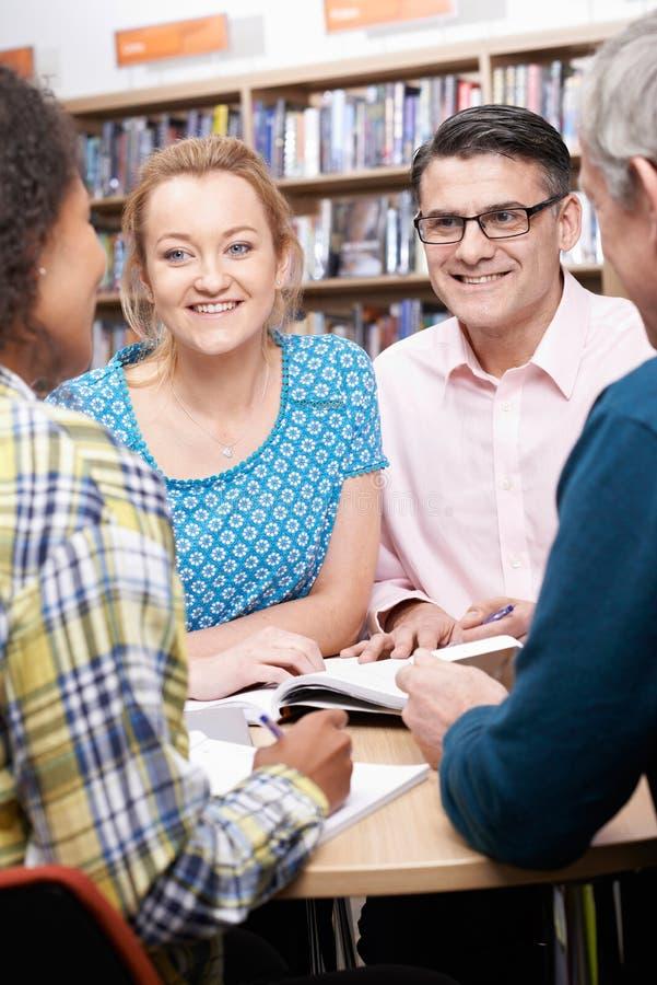 Groupe d'étudiants mûrs étudiant dans la bibliothèque photos stock