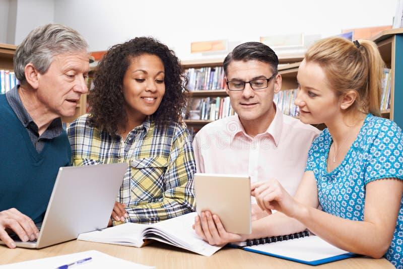 Groupe d'étudiants mûrs étudiant dans la bibliothèque photo libre de droits