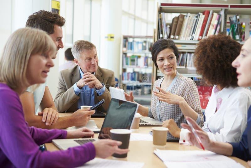 Groupe d'étudiants mûrs collaborant sur le projet dans la bibliothèque photo stock