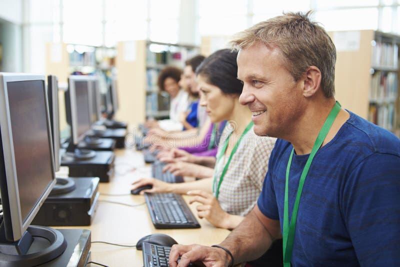 Groupe d'étudiants mûrs travaillant aux ordinateurs photos stock