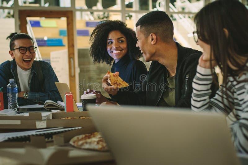 Groupe d'étudiants mangeant de la pizza à la cantine d'université image libre de droits