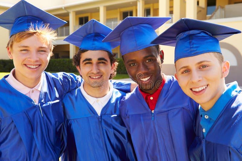 Groupe d'étudiants masculins de lycée célébrant l'obtention du diplôme image libre de droits