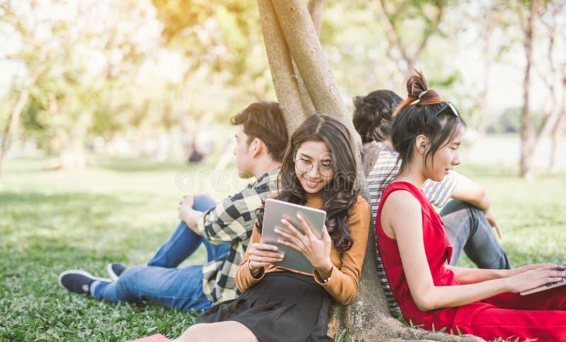 Groupe d'étudiants ou d'adolescents avec l'ordinateur portable et les tablettes traînant photos libres de droits