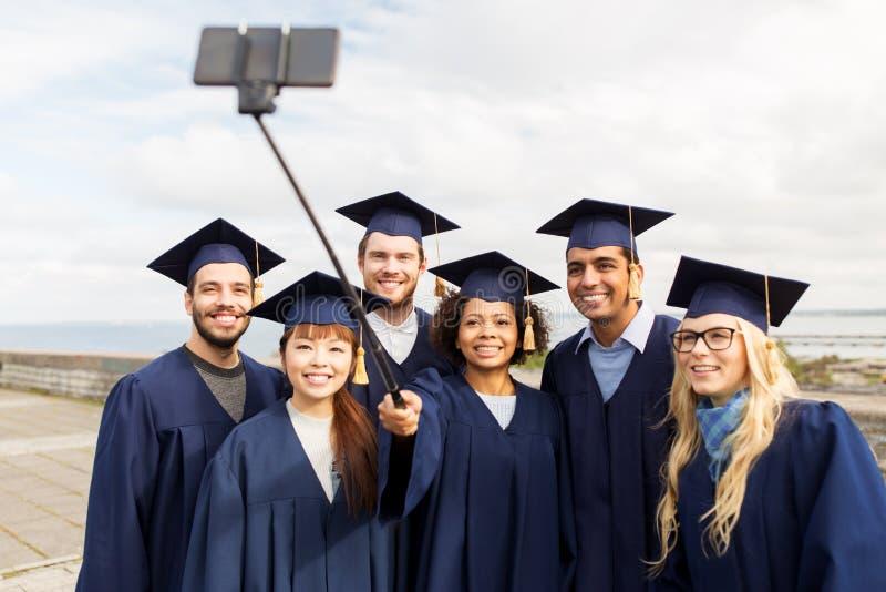 Groupe d'étudiants ou de diplômés heureux prenant le selfie photos stock