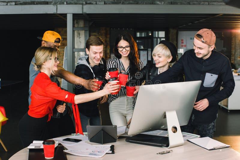 Groupe d'étudiants ou de travailleurs internationaux dans des tasses de bureau de grenier de café tintantes, six collègues de tra photographie stock