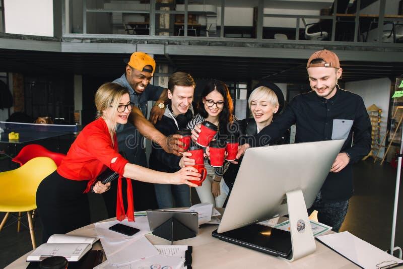Groupe d'étudiants ou de travailleurs internationaux dans des tasses de bureau de grenier de café tintantes, six collègues de tra images stock