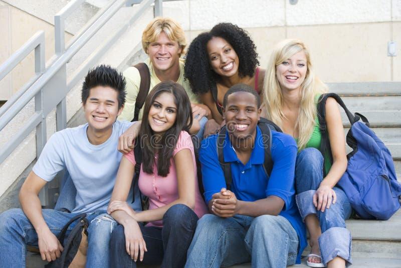 Groupe d'étudiants s'asseyant sur des opérations photographie stock
