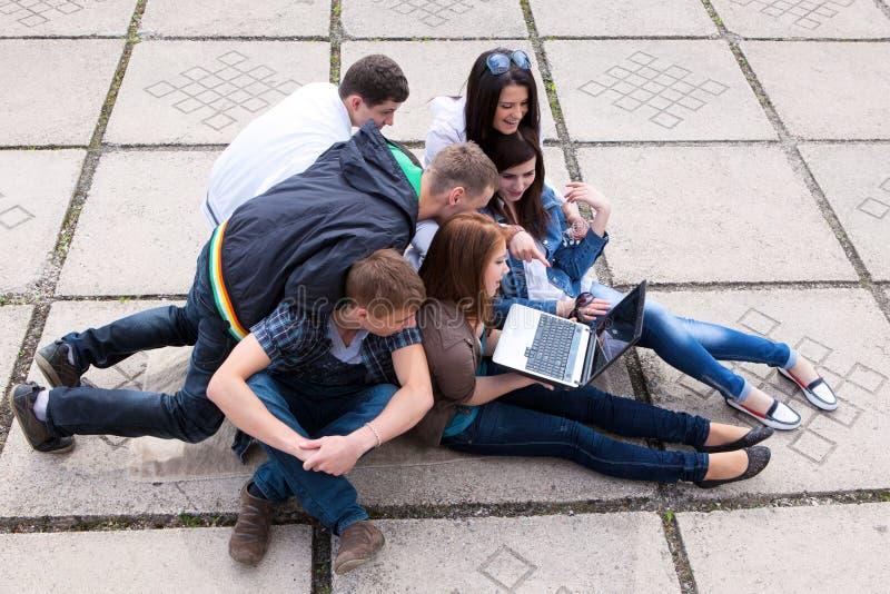 Groupe d'étudiants s'asseyant sur la rue photo stock
