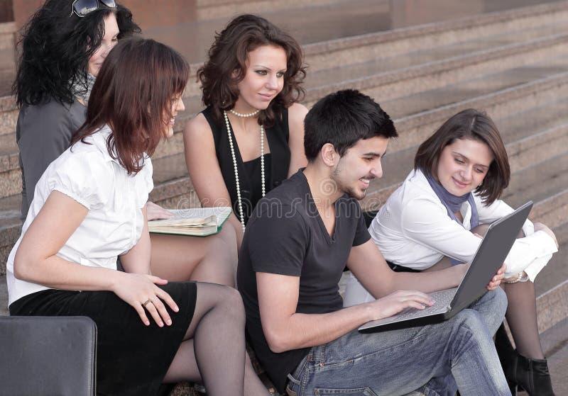 Groupe d'étudiants se préparant aux essais utilisant l'ordinateur portable images stock