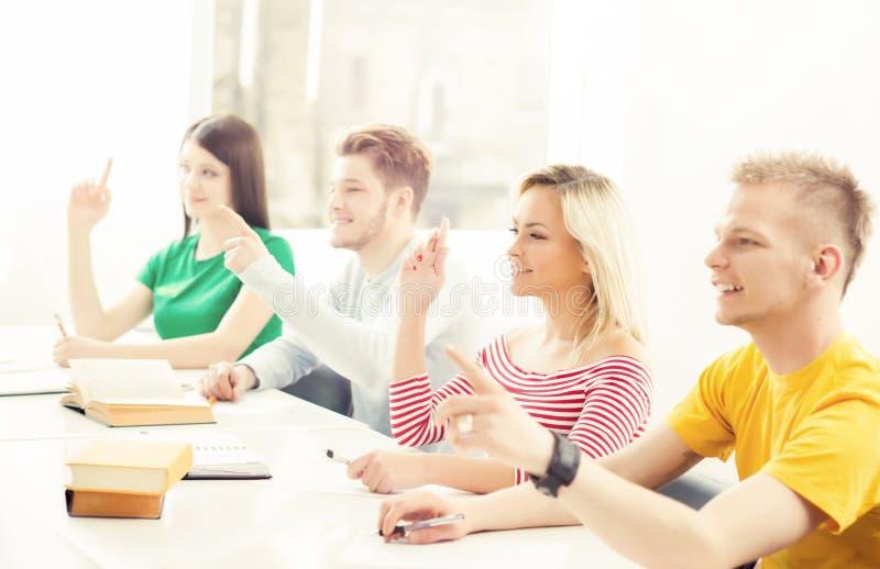 Groupe d'étudiants soulevant des mains Étude d'adolescents dans une salle de classe photo stock