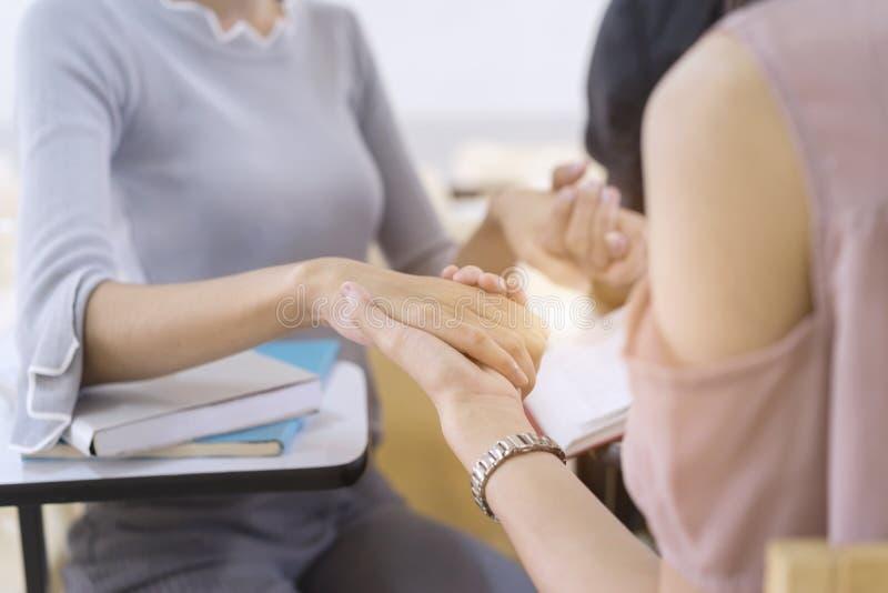 Groupe d'étudiants tenant des mains et priant avant d'apprendre et educ images stock