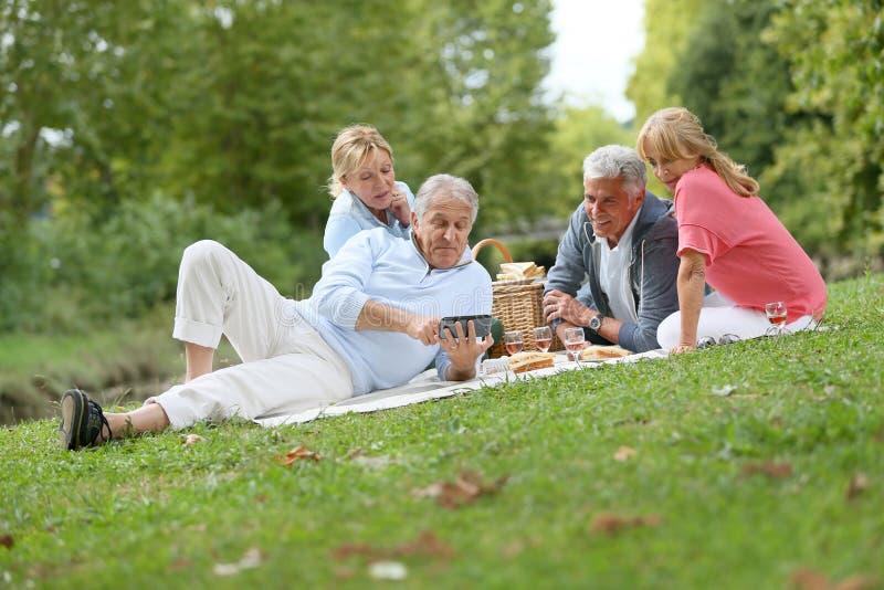 Groupe d'aînés ayant le pique-nique dehors photo stock