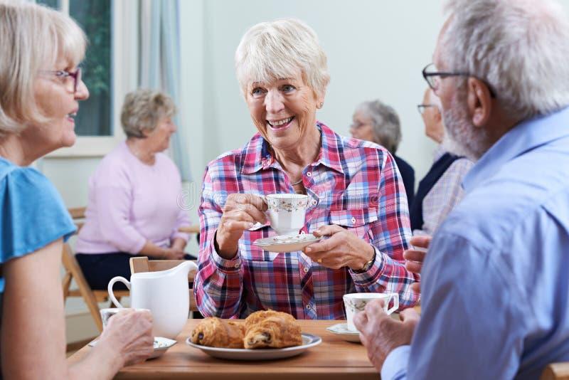 Groupe d'aînés se réunissant au club social image stock