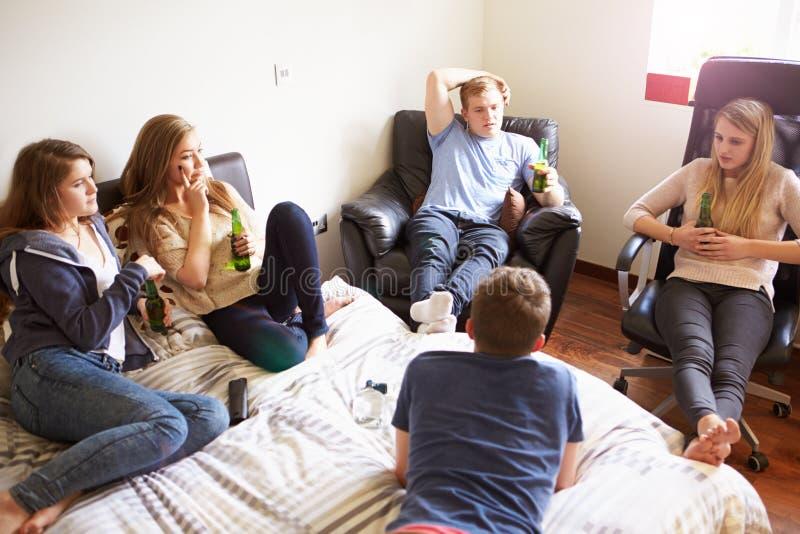 Groupe d'adolescents buvant l'alcool dans la chambre à coucher photo stock