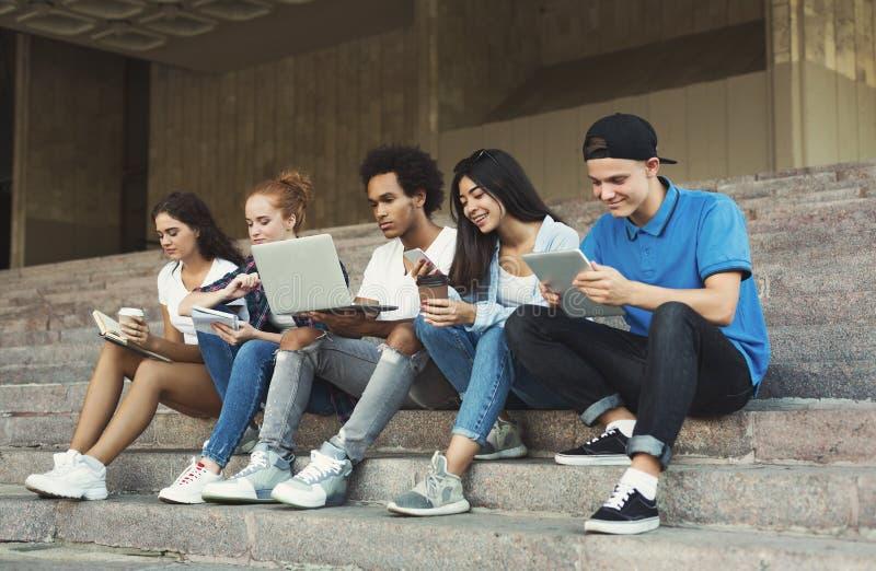 Groupe d'adolescents divers à l'aide des instruments, s'asseyant sur des escaliers extérieurs photographie stock