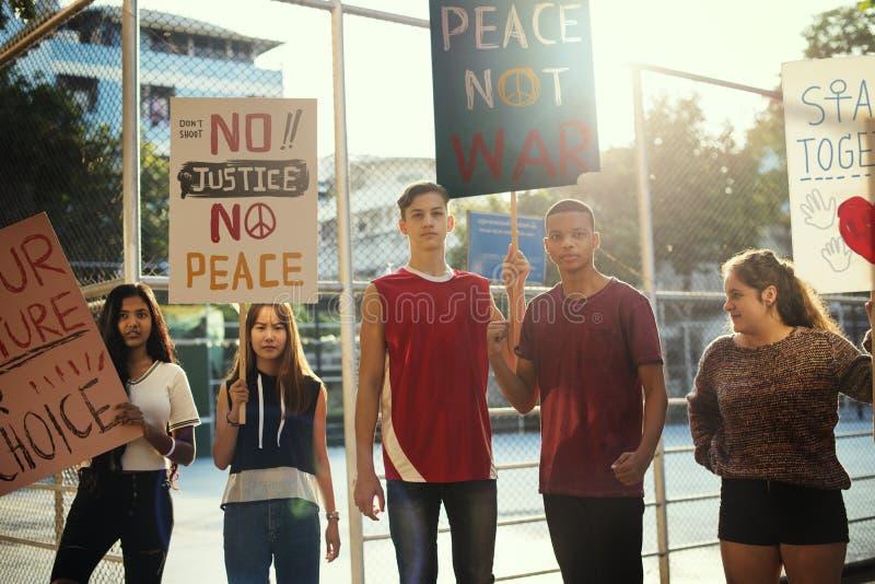 Groupe d'adolescents protestant la démonstration tenant le concept pacifiste de paix de justice d'affiches photographie stock