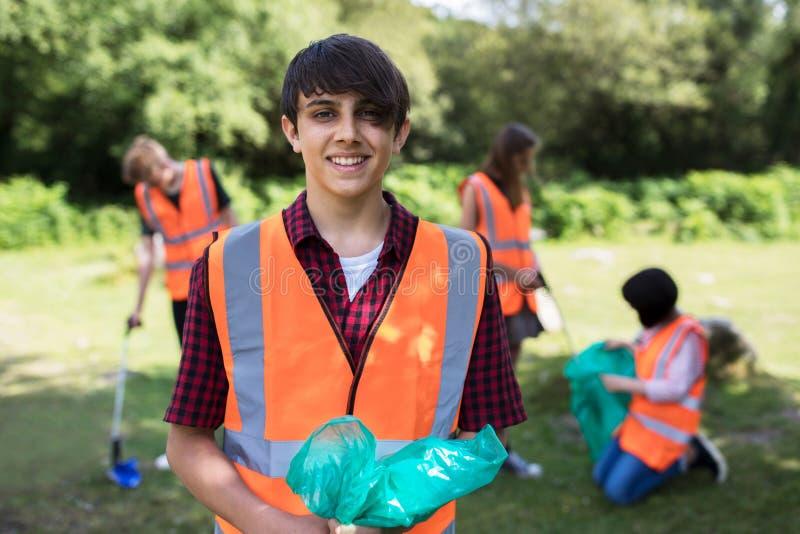 Groupe d'adolescents utiles rassemblant des ordures dans la campagne photographie stock