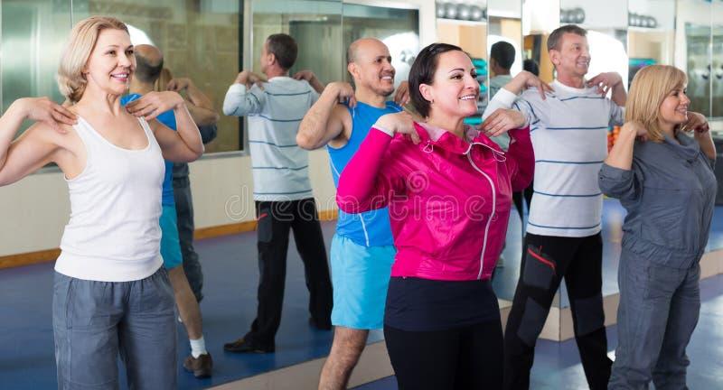 Groupe d'adultes faisant l'exercice d'aérobic dans le club de sport image libre de droits