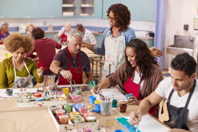 Groupe d'adultes mûrs s'occupant d'Art Class In Community Centre avec le professeur photographie stock libre de droits