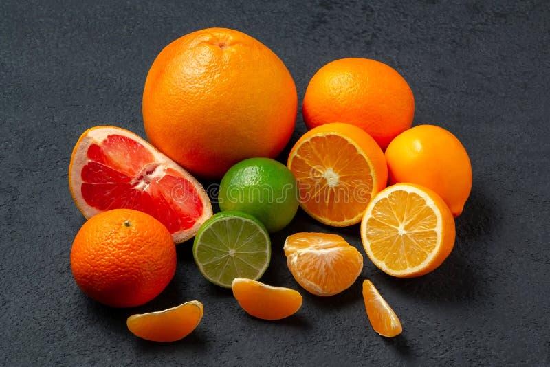Groupe d'agrumes entiers et coupés en tranches - mandarines, citrons, chaux, oranges, pamplemousses sur la surface de l'obscurité image libre de droits