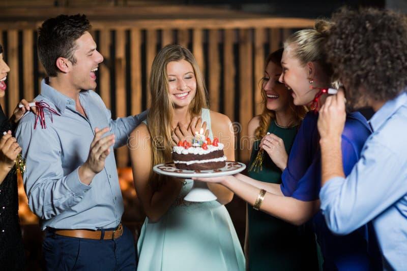 Groupe d'amis étonnants une femme avec le gâteau d'anniversaire photo libre de droits